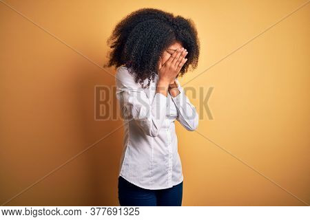 Young beautiful african american elegant woman with afro hair standing over yellow background with sad expression covering face with hands while crying. Depression concept.