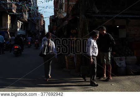 Kathmandu, Nepal - June 20, 2019: Sun shining on nepali man in traditional clothes walking on narrow street in old town, Local daily life
