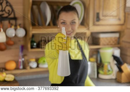 Portrait Of Young Beautiful Housewife In Black Apron Standing With Kitchen Cleaner Spray, Woman Look