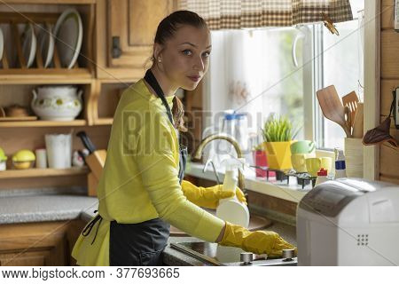 Portrait Of Young Beautiful Housewife In Black Apron Cleaning House Wipes Kitchen Worktop Using Spra