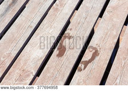 Wet Kid Footsteps On Poolside Deck. Wooden Pier With Wet Footprint. Swimming In Summer. Vacation Rel
