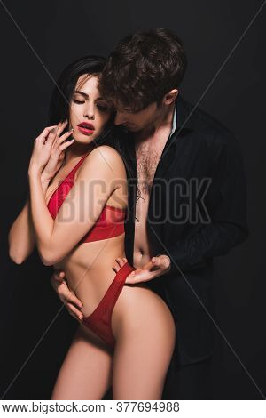 Passionate Man Touching Red Panties Of Seductive Girl Isolated On Black