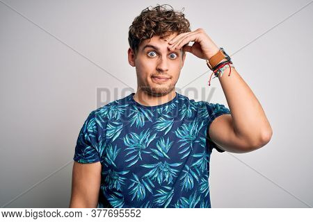 Young blond handsome man on vacation with curly hair wearing casual summer t-shirt worried and stressed about a problem with hand on forehead, nervous and anxious for crisis