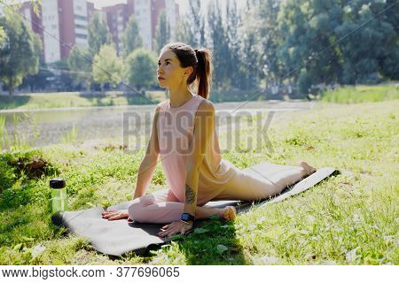 Young attractive woman practicing yoga in nature, doing yoga exercise - ekapada rajakapotasana