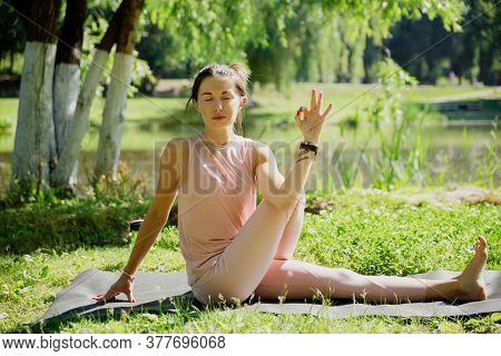 Young attractive woman practicing yoga in nature, doing yoga exercise - mariciasana.