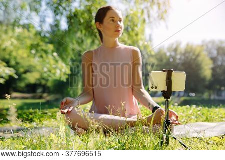 Caucasian female vlogger outdoors, in nature demonstrating exercises for her online blog recording with a camera. Social distancing and self isolation in quarantine lockdown