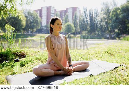 Young attractive woman practicing yoga in nature, doing yoga exercise - baddha konasana