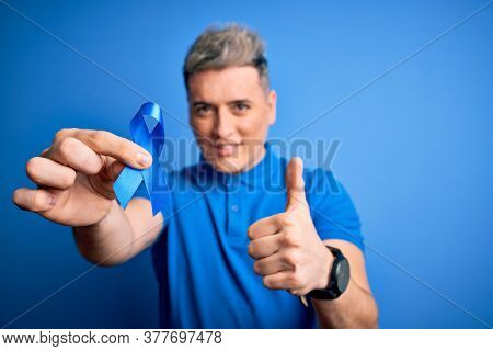 Close up of young man holding colon cancer awareness blue ribbon over isolated background happy with big smile doing ok sign, thumb up with fingers, excellent sign