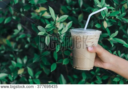 Close Up Hand Holding Glass Of Ice Americano Coffee With Green Leaves Nature Background, Selective F