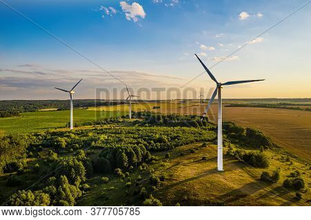 Wind Generators On The Background Of The Setting Sun Top View From A Drone