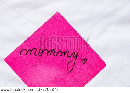 Mommy Handwriting Text Close Up Isolated On Pink Paper With Copy Space. Writing Text On Memo Post Re
