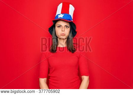 Young beautiful brunette woman wearing united states hat celebrating independence day puffing cheeks with funny face. Mouth inflated with air, crazy expression.