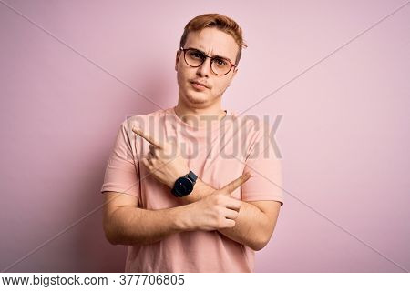 Young handsome redhead man wearing casual t-shirt standing over isolated pink background Pointing to both sides with fingers, different direction disagree