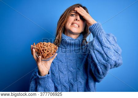 Young beautiful brunette woman holding bowl german baked pretzels over blue background stressed with hand on head, shocked with shame and surprise face, angry and frustrated. Fear and upset