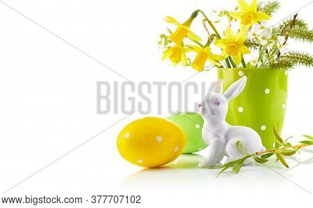 Easter eggs with bunch spring flowers narcissus blooming branch willow and porcelain statuette rabbit. Festive composition side view. Isolated on white background.