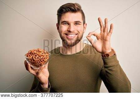 Young blond German man with beard and blue eyes holding bowl with baked pretzel doing ok sign with fingers, excellent symbol