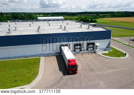 Aerial View Of Trucks Parked In Front Of Industry Building. Aerial.