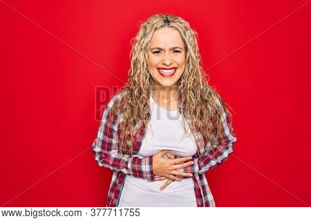 Young beautiful blonde woman wearing casual shirt standing over isolated red background smiling and laughing hard out loud because funny crazy joke with hands on body.