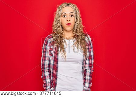 Young beautiful blonde woman wearing casual shirt standing over isolated red background puffing cheeks with funny face. Mouth inflated with air, crazy expression.