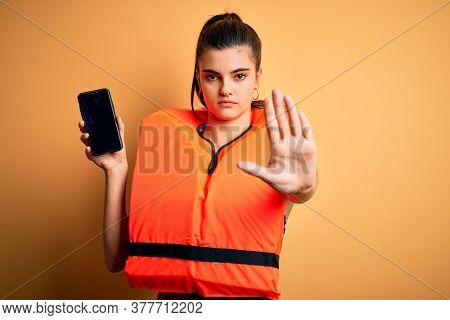 Young beautiful brunette woman wearing safe lifejacket showing smartphone with open hand doing stop sign with serious and confident expression, defense gesture