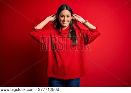 Young beautiful brunette woman wearing casual sweater over isolated red background Smiling pulling ears with fingers, funny gesture. Audition problem