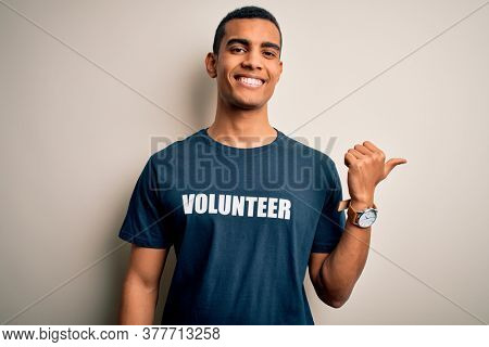 Young handsome african american man volunteering wearing t-shirt with volunteer message smiling with happy face looking and pointing to the side with thumb up.