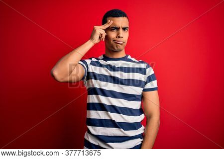 Handsome african american man wearing casual striped t-shirt standing over red background worried and stressed about a problem with hand on forehead, nervous and anxious for crisis