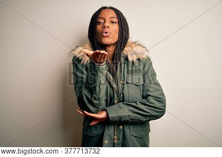 Young african american woman wearing winter parka coat over isolated background looking at the camera blowing a kiss with hand on air being lovely and sexy. Love expression.