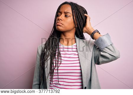 Young african american business woman standing over pink isolated background confuse and wondering about question. Uncertain with doubt, thinking with hand on head. Pensive concept.