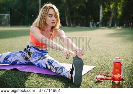 Young woman stretching on a athletic field