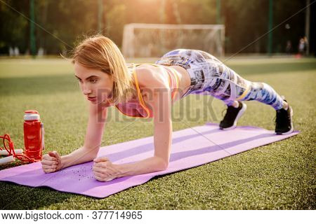 Beautiful young woman in sports wear doing plank exercise on yoga mat