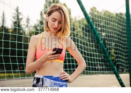 Young blonde woman uses smartphone at the athletic field