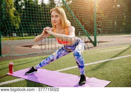 beautiful slim woman stretching her body and doing side lunge exercises at a athletic field