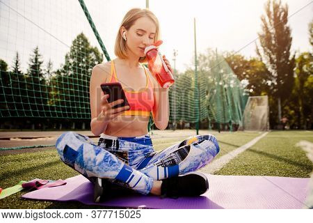 Young woman in sportswear sits on the mat, drinking water from, bottle uses a smartphone and relaxing after sport exercises on sport stadium.