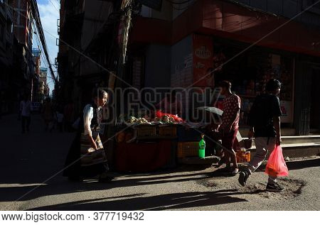Kathmandu, Nepal - June 20, 2019: Sun shining on old woman in traditional tibetan dress walking on narrow street in old town, Local daily life