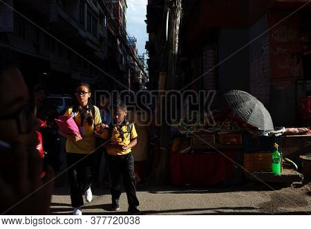 Kathmandu, Nepal - June 20, 2019: Sun shining on two school children brother and sister walking on narrow street in old town, Local daily life