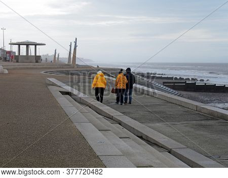 Blackpool, Lancashire, United Kingdom - 6 March 2020: Older People In Anoraks Walking Along The Prom