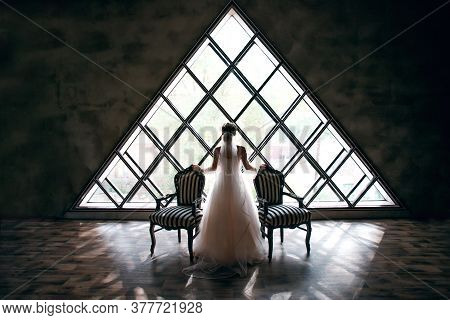 Bride In A Wedding Dress Near Two Striped Armchairs, Black And White, Against A Background Of A Tria