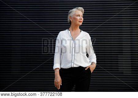 Portrait of beautiful senior woman with white hair on black background.