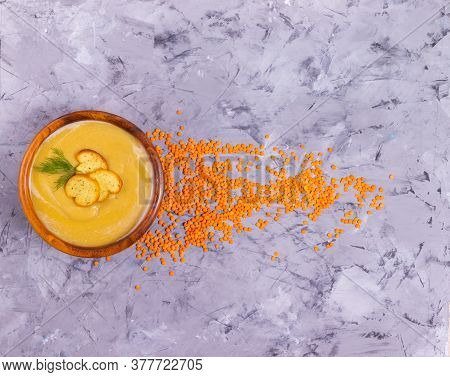 Lentil And Pumpkin Cream Soup With Dill In A Wooden Plate With A Wooden Spoon With Orange Lentils Sc