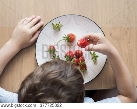 Little Unrecognizable Boy Eats Fresh Strawberry With Relish. Happy Child Eats Organic Strawberry At