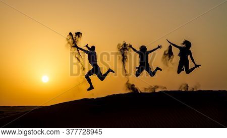 Silhouette Of Happy Traveling People Jumping On Sand Dune And Throwing Sand In The Air In Golden Sun