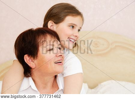 Cute Little Girl Child And Her Grandmother Are Spending Time Together At Home. Having Fun, Hugging A