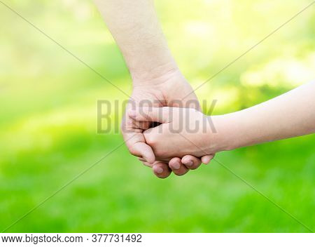 Child Holding Father Hand Outdoors. Care Trust And Helping Concept