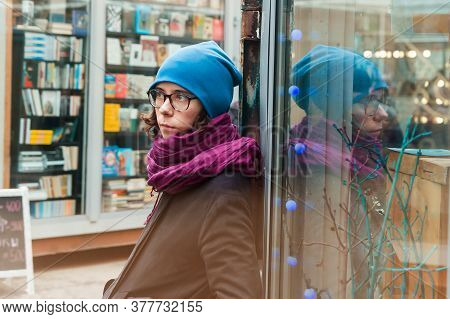 A Girl Waits Leaning To A Window Of A Shop At The Shopping Street