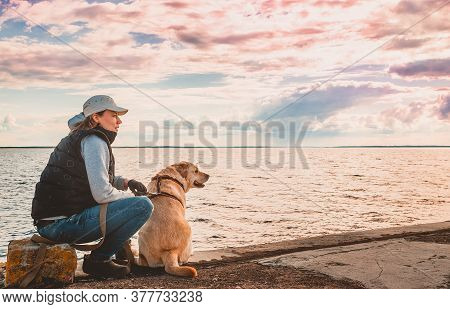 A Girl Is Sitting With A Labrador Retriever On The Quay During A Walk And Admires The View. Evening