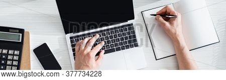 Panoramic Shot Of Man Typing On Laptop And Writing On Notebook Near Stationery And Smartphone On Tab