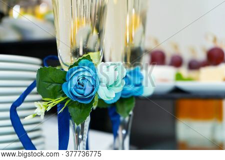 Champagne Glasses Are Decorated With A Blue Ribbon With A Flower. Festive Banquet Table For A Weddin