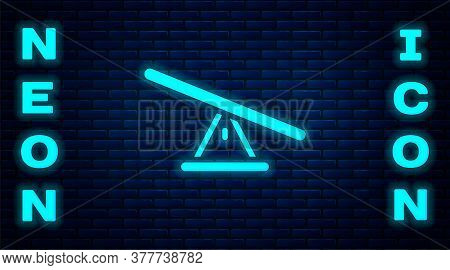 Glowing Neon Seesaw Icon Isolated On Brick Wall Background. Teeter Equal Board. Playground Symbol. V