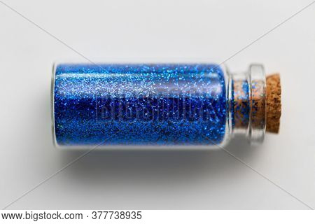 party, decoration and holidays concept - ultramarine blue glitters in small glass bottle with cork stopper over white background